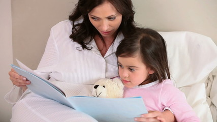 Smiling mother reading a book aloud
