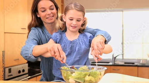 Mother and daughter mixing a salad