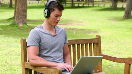 Camera rises to show a man typing on a laptop while wearing headphone