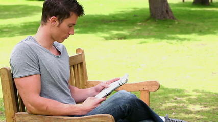 Man reading a newspaper while sitting on a wooden bench
