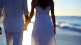Man taking the hand of his girlfriend before they walk towards the sunset on the beach
