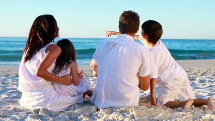 Happy family sitting on the sand