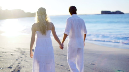 Couple on the beach walking towards the sunset while holding hands