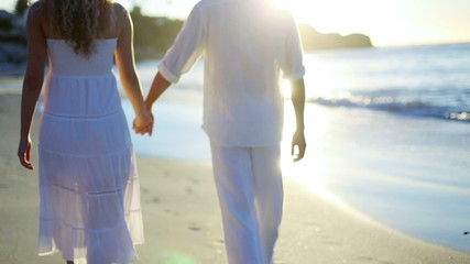 Man taking his girlfriends hand before they walk towards the sunset on the beach