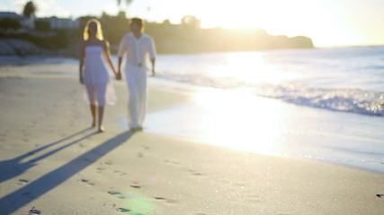 Couple holding hands as they walk away from the sunset on the beach