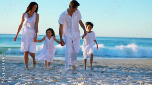 Family walking on beach hand in hand