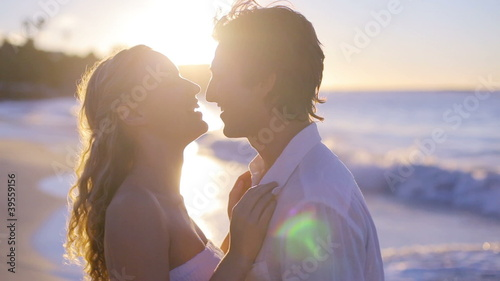 Couple kissing and turning during sunset on the beach