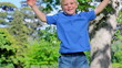 Boy jumping in a park with his arms raised
