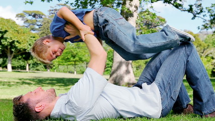 Father lies on the grass and raises his son in the air as he pretends to be and airplane