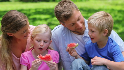 Family sitting together while eating slices of watermelon