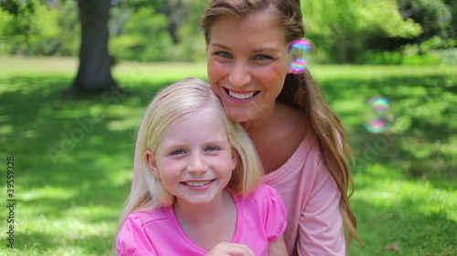 Mother sitting with her daughter who is blowing bubbles