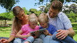 A family reads a book as they sit together in a park before
