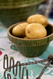 A vintage bowl full of potatoes and antique masher