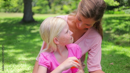 A mother helps her daugther to blow bubbles