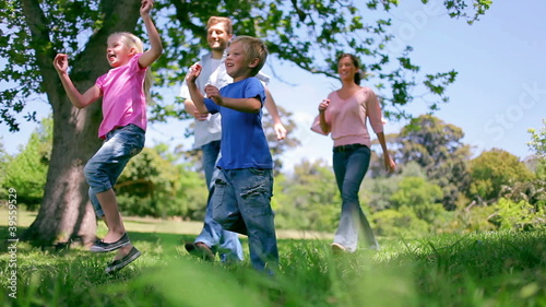Low angle view of a family skipping together through grass