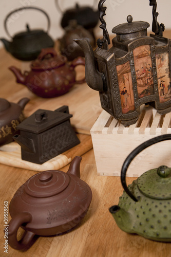 A collection of antique ceramic Asian teapots