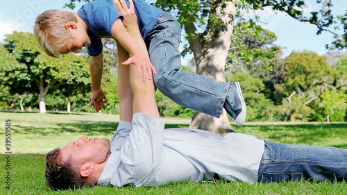 A father lifts his son above him as he lies on the