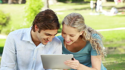 A smiling couple use a tablet pc in the park as they look