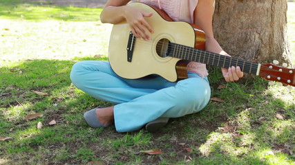 Camera rises to show a girl playing guitar in the park