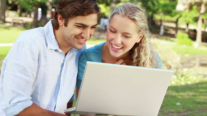 A happy couple in the park with a laptop laughing as they