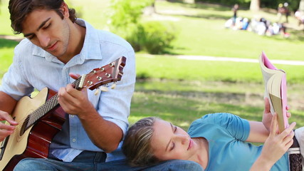 Man practises on the guitar as the woman reads her