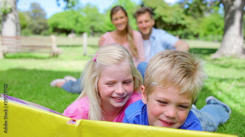 Two kids reading a book together while smiling and looking at