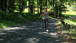 A woman jogs in the park and then is jogging on a main road