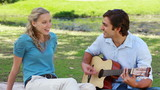 A man plays guitar and sings to a woman as they sit