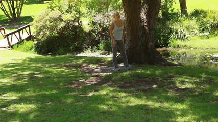 A woman jogs in the park as she stops by a tree and moves