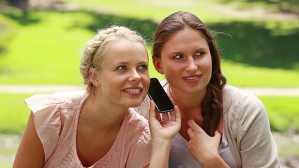 Two shocked women listen to someone on the phone
