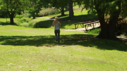 A woman jogs in the park away from the camera