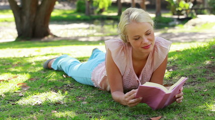 A woman lying down reading a book in the park as
