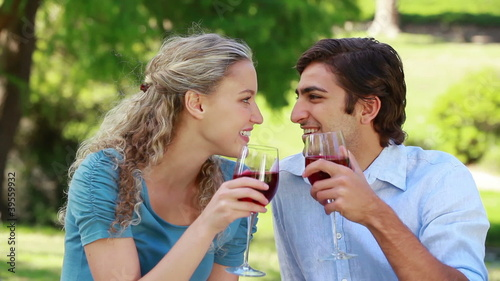 A couple sit and talk as they clink their wine glasses