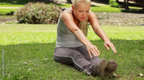 A woman stretches out in the park