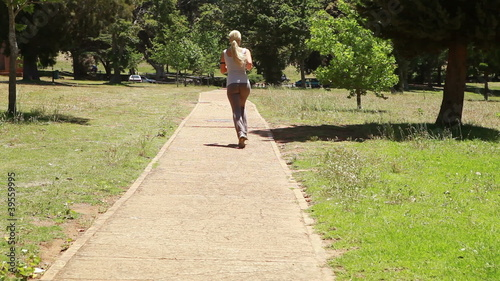 Jogging woman runs down the footpath