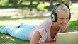 A woman lies in the park with headphones on while watching a laptop