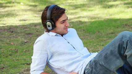 A man lies on the ground listening to his headphones