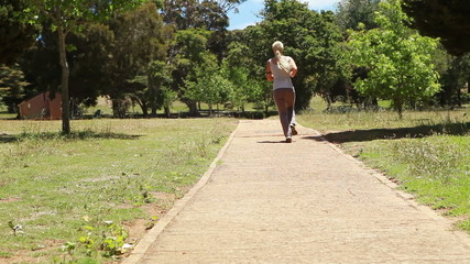 A woman jogs past the camera and down a footpath