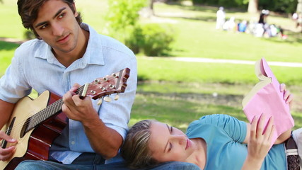 Man practises guitar as the woman rests on his leg and reads