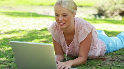 A woman lying in the park with her laptop as she then looks at the camera
