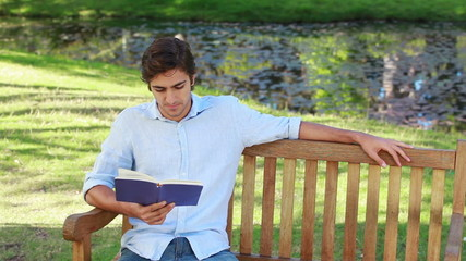 Man sits on a bench while reading a book