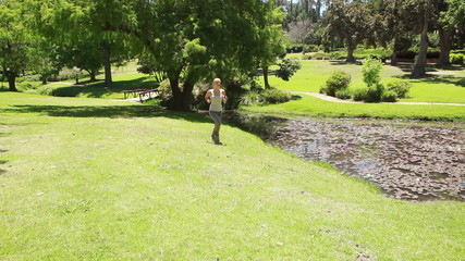 A woman jogs in the park as she runs past the camera