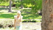 A woman walks up towards a tree talking on her phone