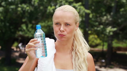 A woman takes a sip of water the wipes her head before drinking again