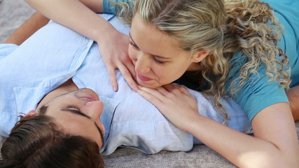 A woman lying on a man's chest talks to him as they smile