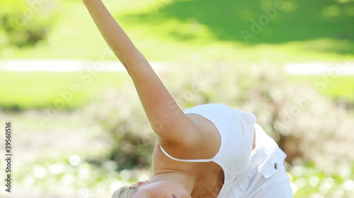 A woman performs yoga while the camera pans downwards