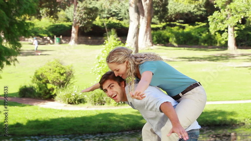 A man gives his girlfriend a piggy-back as they look at the camera