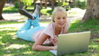 A woman lies in the park with her laptop as she laughs and then looks at the camera