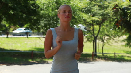 A woman jogs while looking around