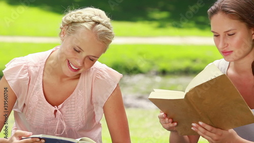 The camera pans across two women reading books